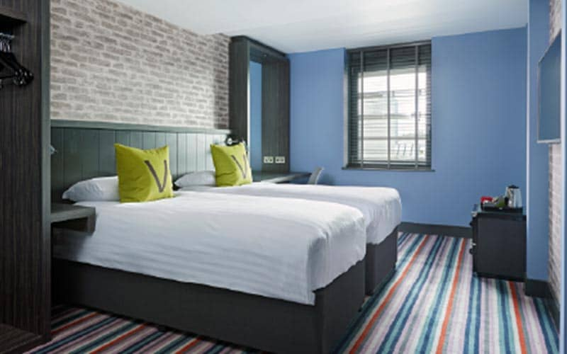 A double bed in a blue hotel room, topped with green cushions with the letter V on