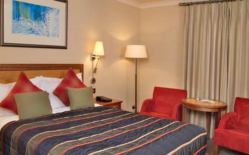 A double room with a red and yellow colour scheme in The Cambridge Belfry