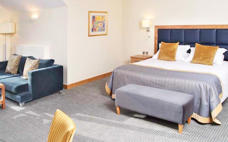 A double room in The Oxford Belfry with a blue sofa and a foot stool at the bottom of the bed