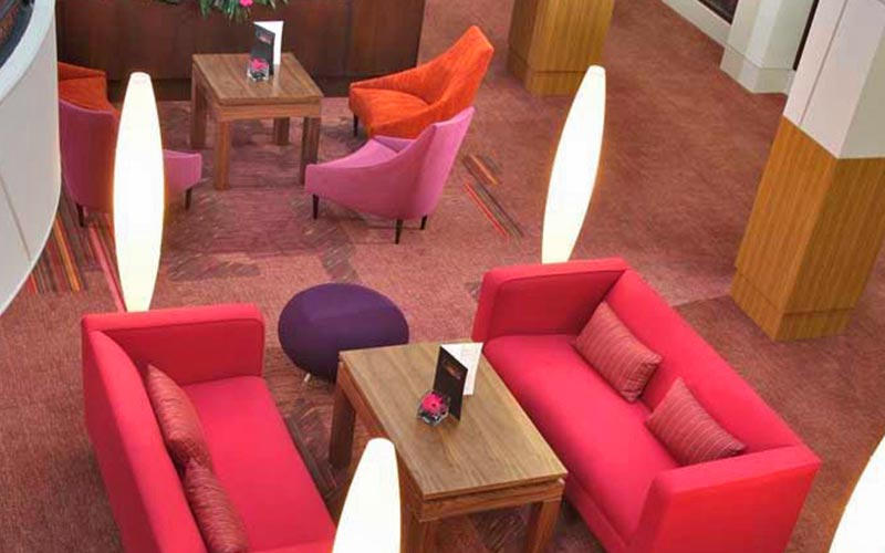 Comfy pink sofas and chairs around wooden coffee tables