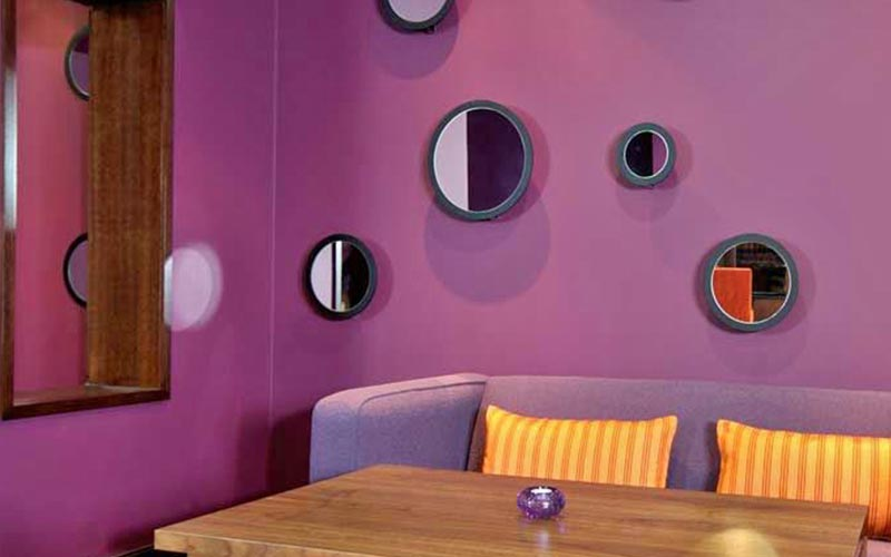 Circular mirrors on a purple wall, above a wooden coffee table and a purple sofa with orange cushions