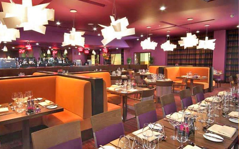 Tables and chairs and orange booths in the restaurant at Ashford International Hotel