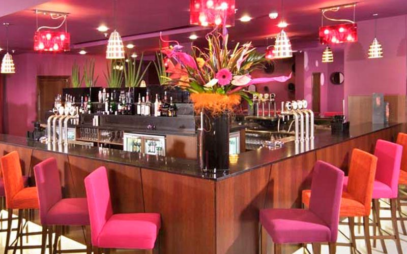Pink and orange bar stools around a bar at Ashford International Hotel