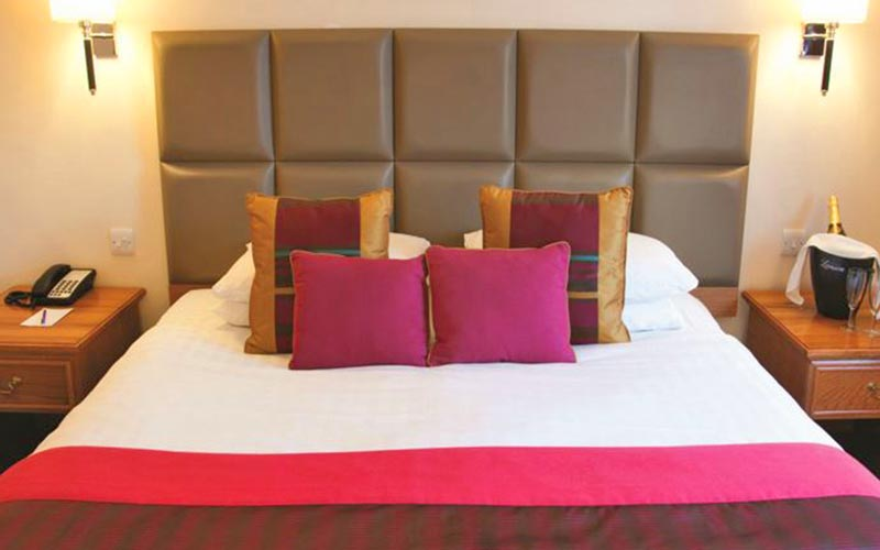 A double bed in a hotel room, topped with a pink throw and cushions, with bedside tables on either side