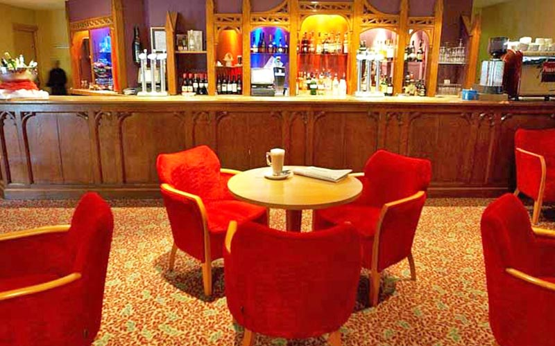 Red chairs around tables at the bar at Bridgewood Manor