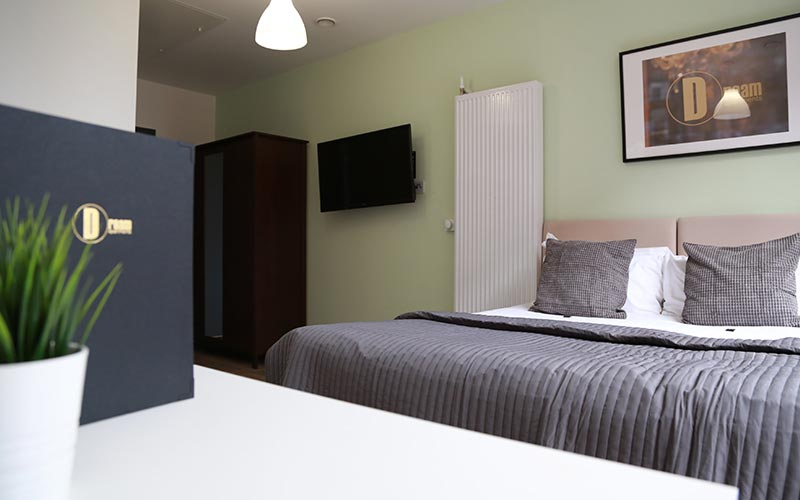 A guest bedroom with a double bed and TV mounted on the wall