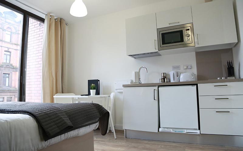 An apartment with a bed and a kitchen area