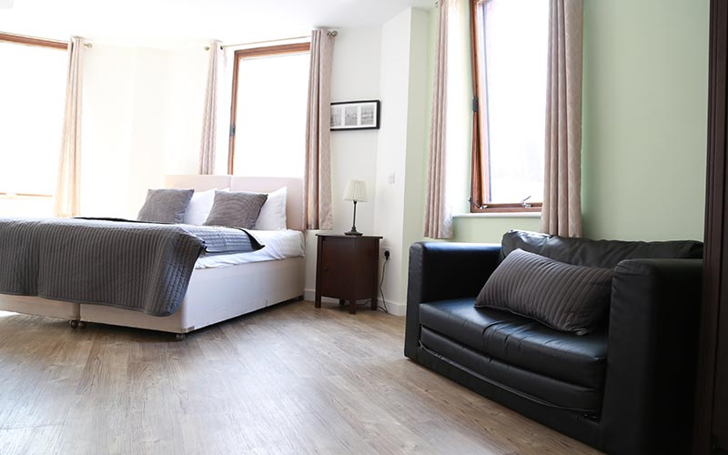 A guest apartment with a double bed and black leather sofa