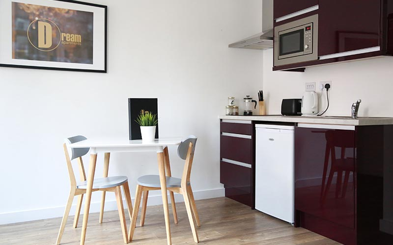 An apartment with a kitchen area and table and chairs