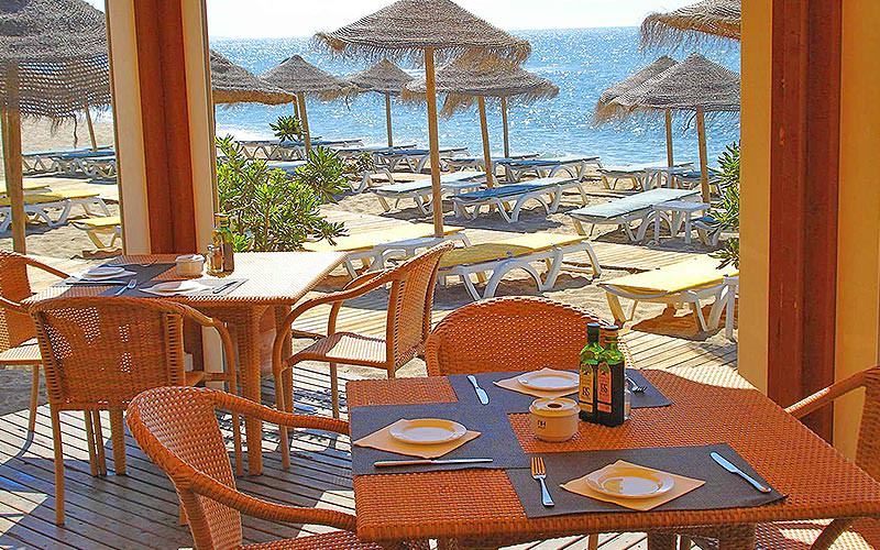 Tables and chairs in a restaurant, with windows looking out to the sun loungers on the beach and the sea