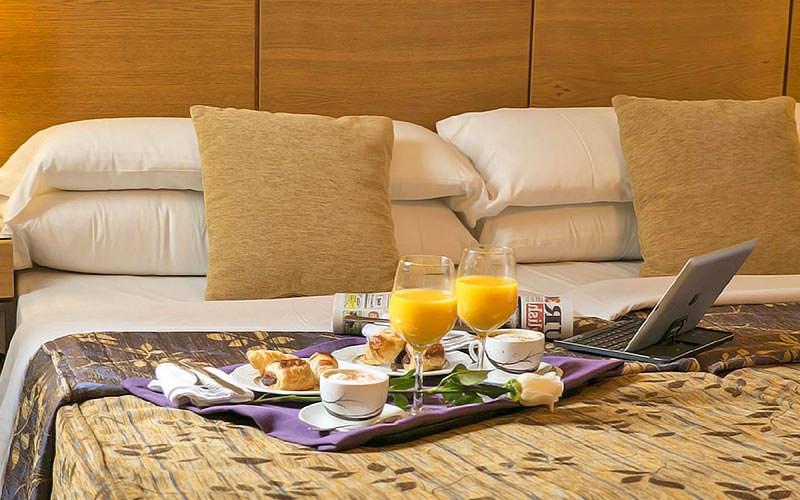 A double bed topped with cushions, with a tray featuring juice and breafast placed next to a laptop