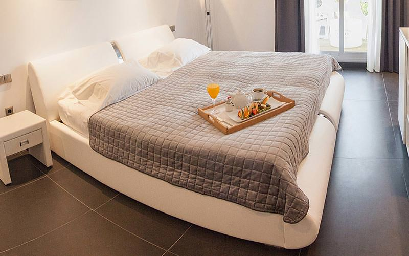 A double bed topped with a throw and breakfast tray, with a bedside table in the corner