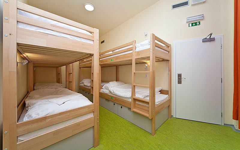 Two rows of bunk beds against the walls of a hostel room with a green carpet