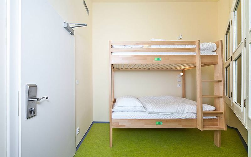 A wooden bunk bed against the wall of a hostel room with a green carpet
