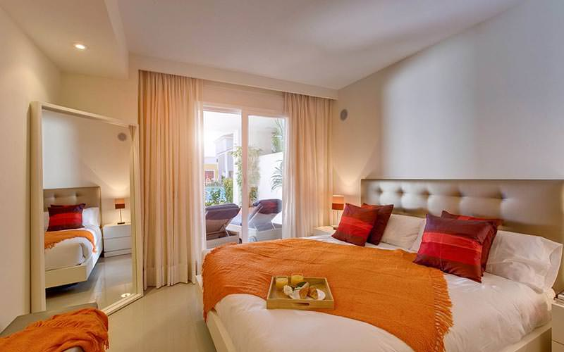 A double bed topped with an orange throw and striped cushions, facing a large mirror in the corner of the room