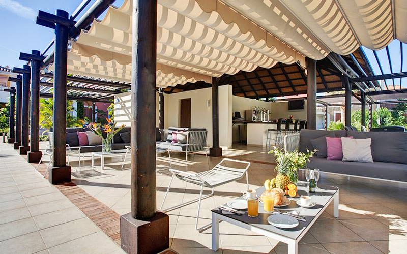 Sofas, chairs and tables under a wooden canopy