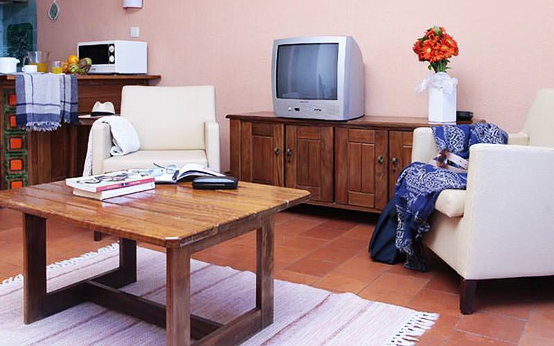 A coffee table with chairs, a TV and kitchenette in the background