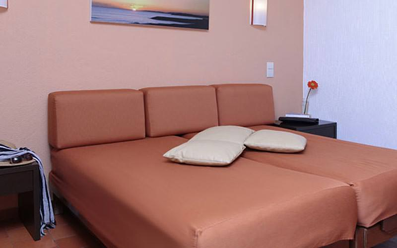 A bed topped with white cushions in a hotel room