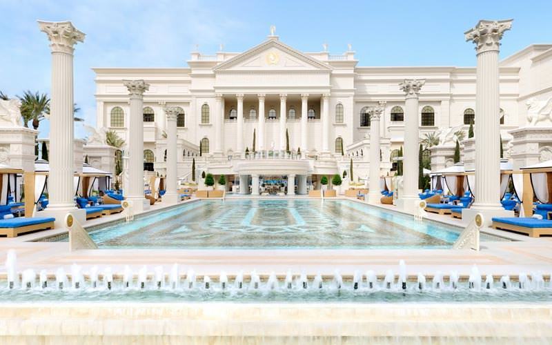 An outdoor swimming pool and the palatial exterior of Caesars Palace