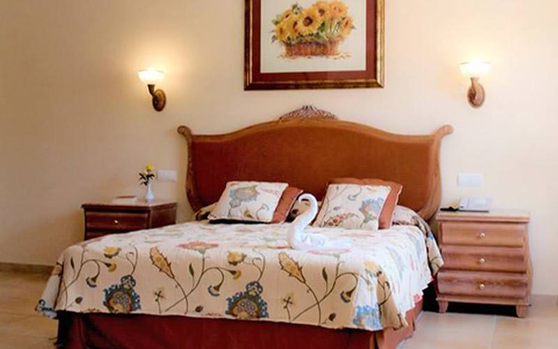 A double bed topped with cushions and floral bedding, with wooden bedside tables on each side
