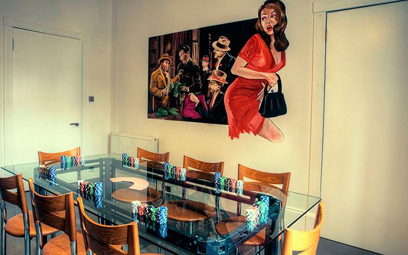 A glass topped table with a mural painted upon the wall