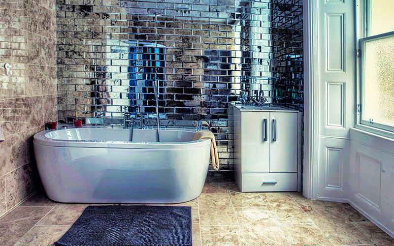 A modern bathroom with shiny tiles, a large window and a white bath tub