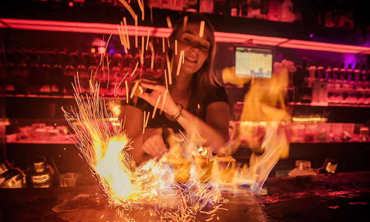 A girl making shots on fire