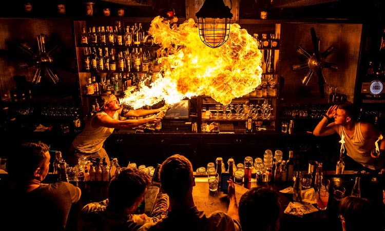 A man blowing fire behind a bar