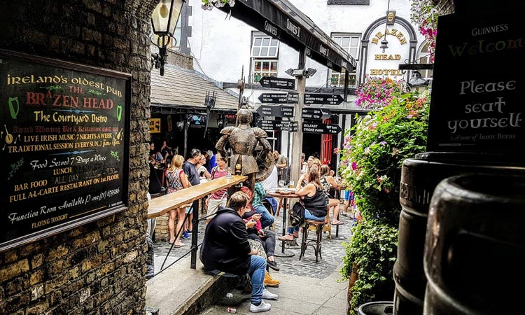 People sat in the beer garden at The Brazen Head, during the day