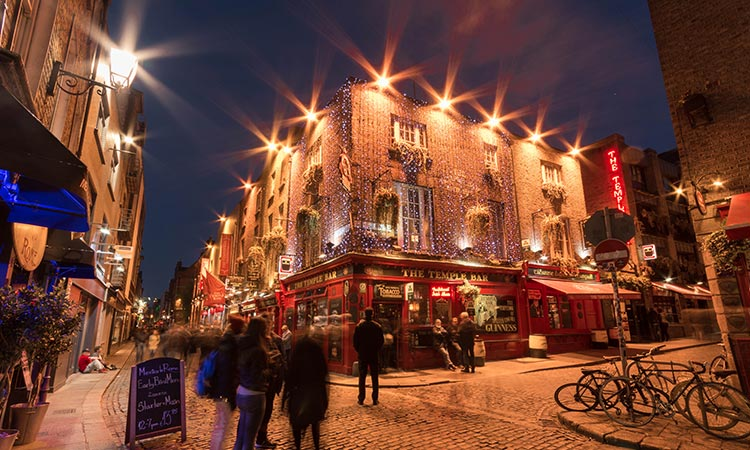Exterior of The Temple Bar pub at night, with people in the street