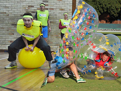Split image of a man boucing on a yellow space hopper and of 3 guys in zorbs bouncing into each other.
