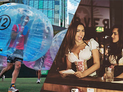 Man in red t-shirt running in an inflated zorb and two women standing at the bar looking towards the camera