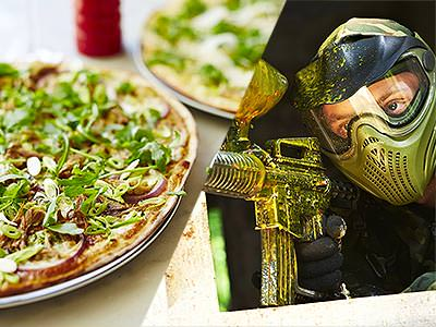 Split image of a pizza topped with rocket, and a man in a mask aiming with a paintball gun
