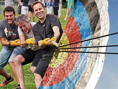 A split image of three men playing tug of war and some arrows sticking out of a target