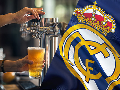 A man pulling a pint and the Real Madrid football badge on a flag