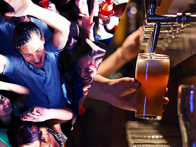 A group of men in a nightclub and a barman pouring a pint