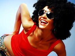 A woman wearing a black afro, sunglasses and a red top leaning over and smiling