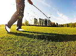 A person following through after hitting a golf ball from a golf course