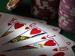 Line of four cards in front of purple poker chips