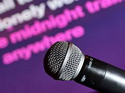 A microphone with lyrics on the screen in the background