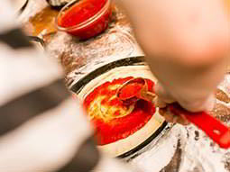 An underarm shot of someone spreading tomato sauce on a pizza base