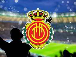 Real Mallorca football logo over a silhouette of a man celebrating at a football ground