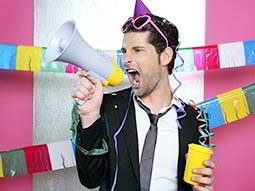 A man in a suit, shouting through a megaphone whilst holding a drink and wearing a party hat