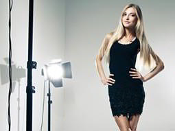 A woman in a black dress posing in a studio next to a light