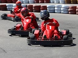 Three people driving red go karts on a outdoor track
