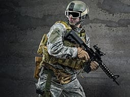 A man wearing army gear with goggles on holding a airsoft gun