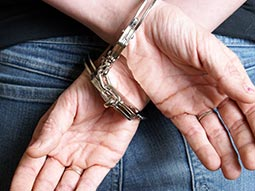 A close up of a man with his hands handcuffed behind his back