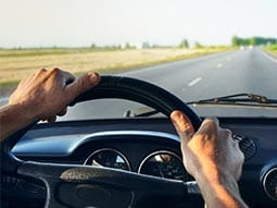 Image of two hands steering a car on a road
