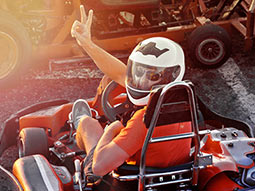 Someone in a go-kart turning around and showing the peace sign