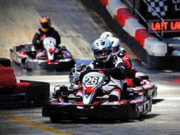 A line of people in go-karts on a track, racing